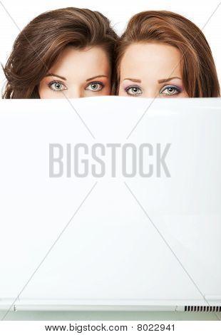 Girls Peeking Behind Laptop
