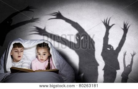 Two little kids reading book under blanket