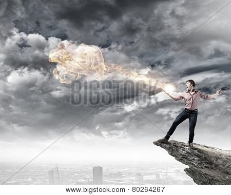 Young man in casual throwing magic fire balls poster