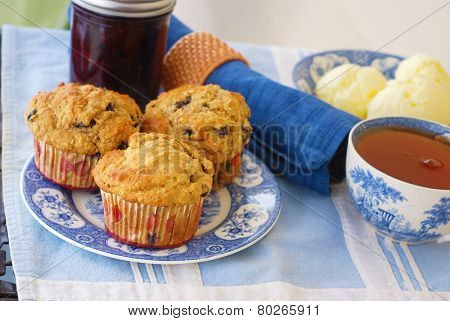 Vintage plate of whole grain (wheat/oat/almond) blueberry muffins with blueberry jam, fresh butter, and cup of hot black tea