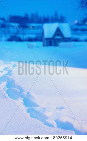 Fresh footprints in deep winter snow at twilight