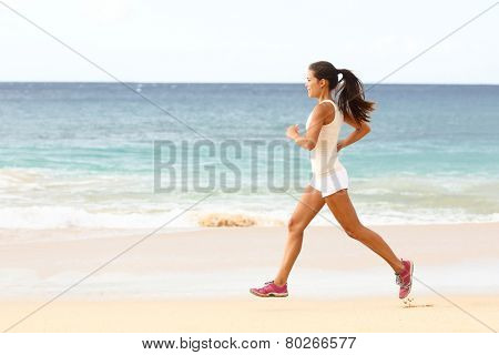 Fit young woman running along the edge of the surf on a sunny tropical beach in her sportswear with her long hair. Female runner exercising with copyspace