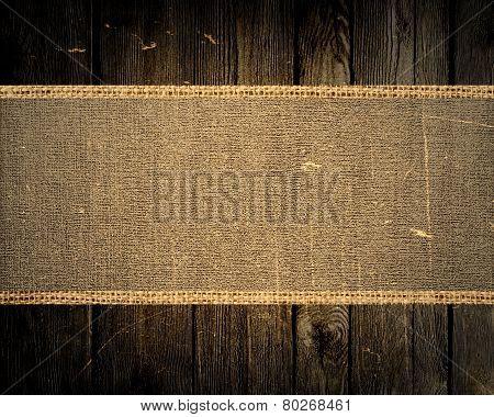 old grunge jute canvas banner textured with dark wood background