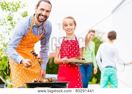 Father and daughter barbecue meat spits and sausages at family garden BBQ