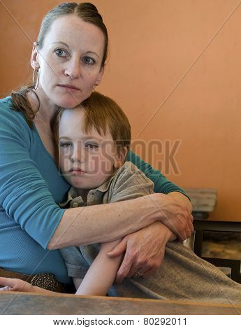 Mother holding and comforting sad young son