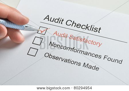Person Hand Making Tick In Audit Checklist