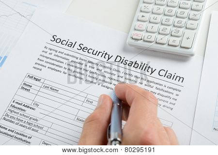 Close-up Of Person Hand With Pen And Calculator Filling Social Security Disability Claim Form poster