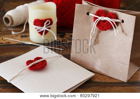 Saint Valentine decoration: handmade crochet red heart for greetings card gift package and candle. Selective focus poster