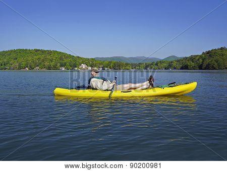 Older Man In Kayak On Mountain Lake