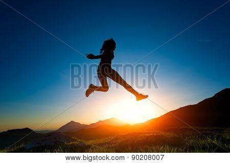 Girl Jumps During A Sunset In The Mountains
