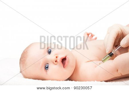 Pediatrician giving a three month baby girl  intramuscular injection in arm. Child looking anxiously at a camera. Isolated on white background.