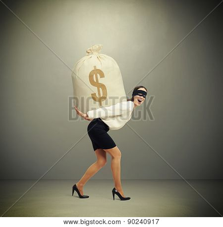 laughing woman in formal wear and black mask on the eyes holding big bag with money and looking at camera against grey background