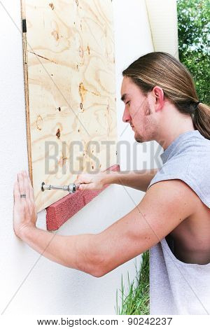 Young man boarding up windows to prepare for natural disaster such as hurricane or tornado.