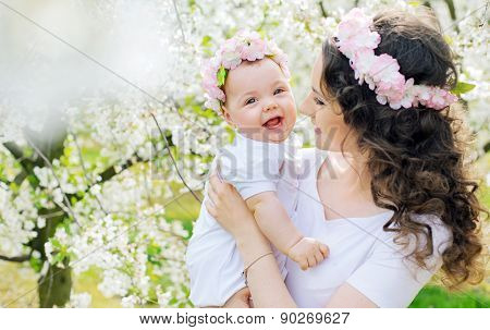 Young mother and her little baby relaxing in a spring orchard