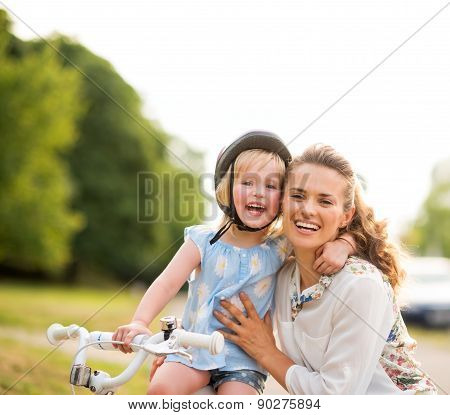 Proud Girl On A Bicycle Hugging Her Mother In A City Park