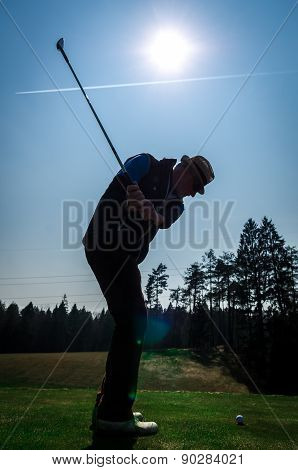 Silhouette Of Old Man Playing Golf. Senior Citizen Is Wearing A Hat And Swinging The Club With Sun A