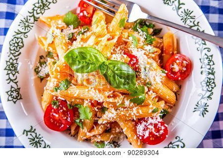 Plate with pasta pene Bolognese sauce cherry tomatoes parsley top and basil leaves