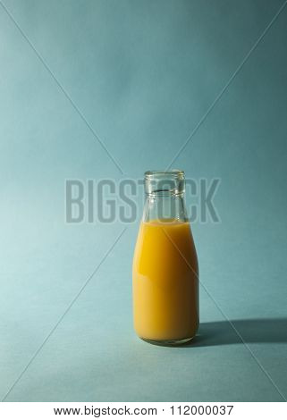 Glass of Orange Juice on Teal Background