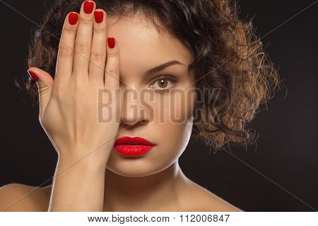 Young attractive lady covering half of her face.