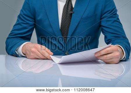 Professional newscaster reading his papers.
