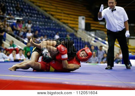 JAKARTA, INDONESIA - NOVEMBER 18, 2015: Luan Zhang of China (red) fights Sanathoi Yumnam of India (black) in the women's 52kg Sanda event finals at the 13th World Wushu Championship 2015 in Jakarta.