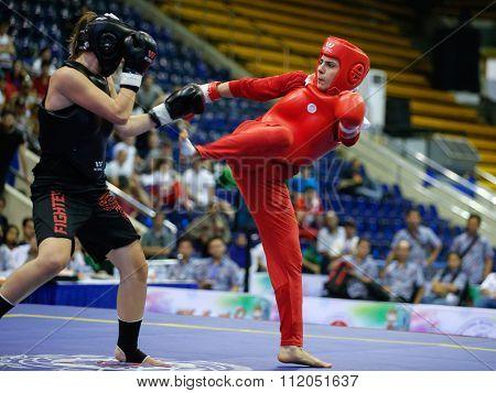JAKARTA, INDONESIA - NOVEMBER 18, 2015: Maryam Hashemiforoud of Iran (red) fights Veronika Kohutova of Czech Rep. (black) in the women's 70kg Sanda finals at the 13th World Wushu Championship 2015.