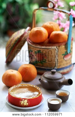 Traditional gift of glutinous rice cake and basket of mandarin oranges in celebration of chinese new year spring festival