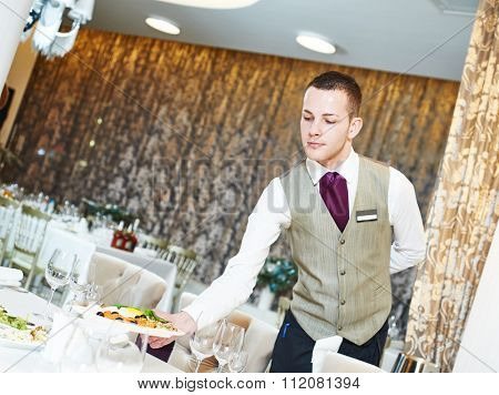 Restaurant catering services. Male waiter with food dish serving banquet table
