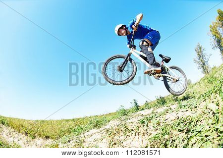 Bicycle extreme sport jump. Young cyclist high jumping downhill on the mountain bike cross-country