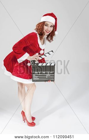Full Length Portrait Of Female Santa Helper Holding Clapperboard In Front Ready To Set Off Filming.