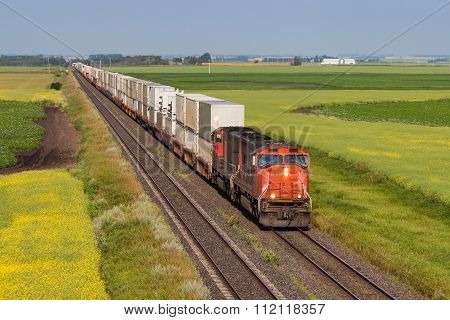 Container Train Across Green And Yellow Prairie