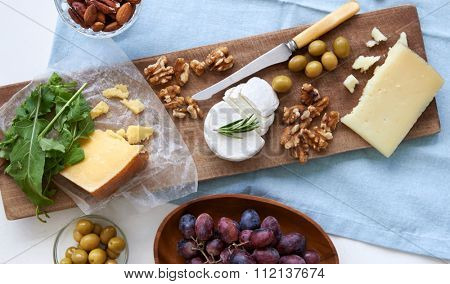 Cheese platter starter appetizer dinner snack, assortment of different cheeses, nuts, olives and grapes