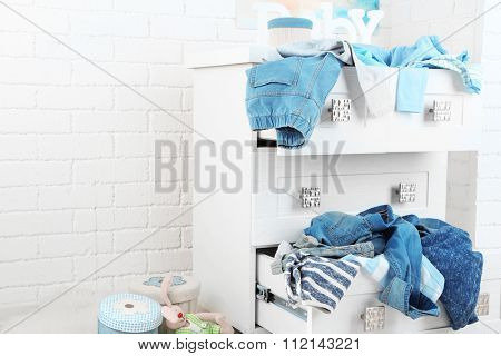 Child clothes in wooden chest of drawer, close up