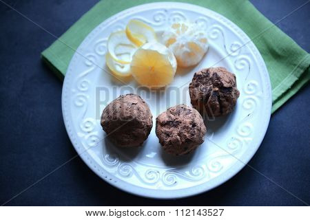 Chocolate balls with lemon on plate on dark blue background