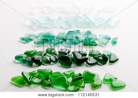 wet glass pieces polished by the sea closeup on white background