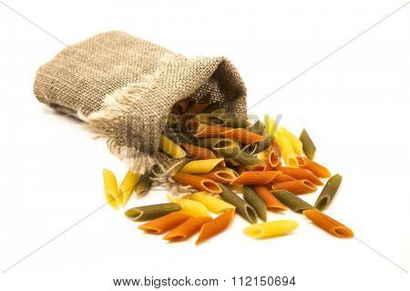 Beautiful Italian pasta Penne rigate from durum wheat  in a linen sack, closeup on a white background.