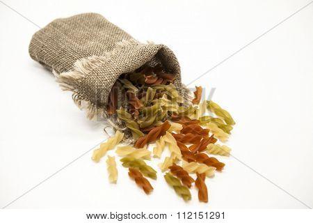 Beautiful Italian pasta Fusilli from durum wheat  in a linen sack, closeup on a white background.