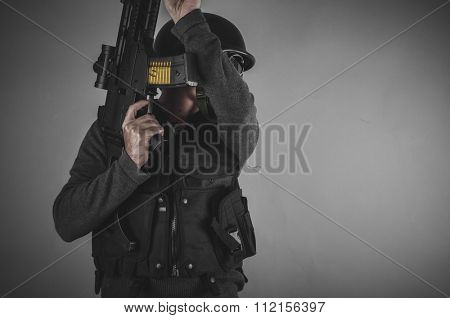 sport airsoft player with gun, helmet and bulletproof vest on gray background