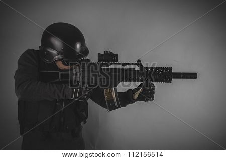 sniper, airsoft player with gun, helmet and bulletproof vest on gray background