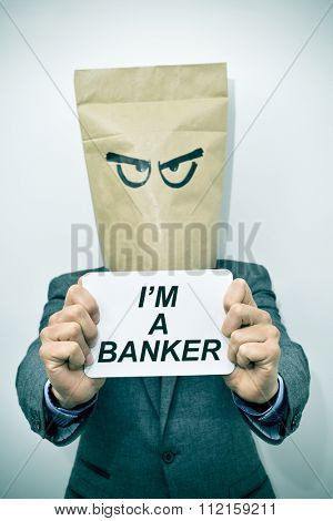 a young caucasian businessman with a paper bag in his head shows a signboard with the text I am a banker, with a dramatic effect
