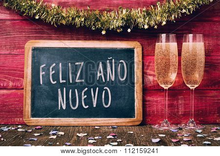 a chalkboard with the text feliz ano nuevo, happy new year written in spanish, some confetti and a pair of glasses with champagne on a red rustic wooden background ornamented with tinsel