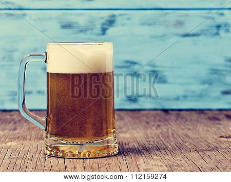 refreshing beer served in a glass mug on a rustic wooden surface, against a blue rustic wooden background