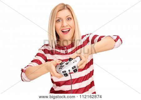 Excited young woman playing video games with a gamepad and looking at the camera isolated on white background