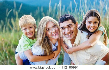 Happy family enjoying vacations otdoors with blurred field on background