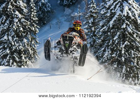 snowmobile in winter forest in the mountains