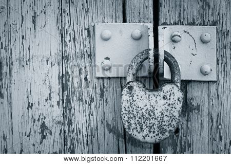 Rusty Padlock On An Old Painted Wooden Gate