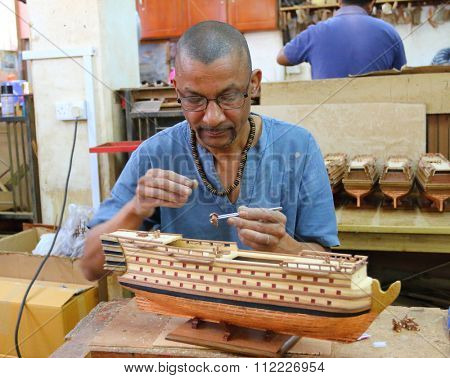 CUREPIPE, MAURITIUS ISLAND - 28. OCTOBER, 2015: Unidentified African worker making souvenirs (ship models) for visitors of Mauritius. Traditional handicraft.