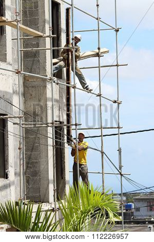 CUREPIPE, MAURITIUS ISLAND - 28. OCTOBER, 2015: Unidentified African workers on a scaffold build new touristic resort on the Mauritius coast.