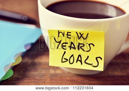 closeup of a cup of coffee with a yellow sticky note with the text new years goals written in it and a notebook and a pen on a rustic wooden table