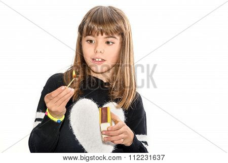 Eight Year Old Girl Playing With Matches Isolated On White